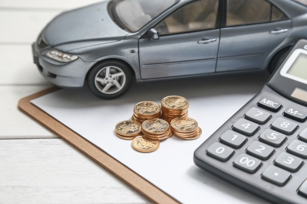 car model calculator and coins on white table 1387 584